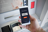 Withdraw money from an ATM without using a credit card. Person holding a phone with a login screen for mobile banking.