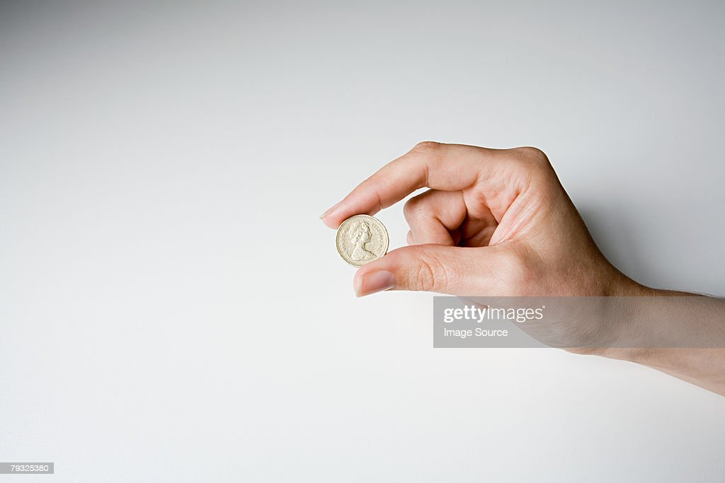 A person holding a pound coin : Stock Photo