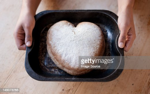 Person holding a tray with heart shaped cake : Stock Photo