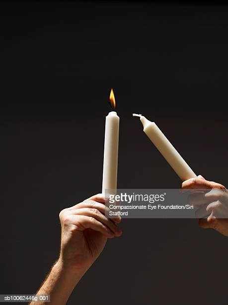 Person holding aloft burning candle, trying to light another one, close-up of hands