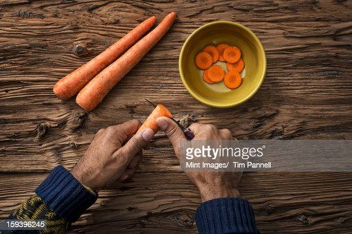 A person holding and slicing fresh carrots into a bowl. : Stock Photo