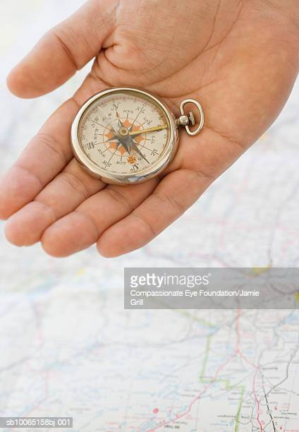 Person holding compass over map, close-up of hand