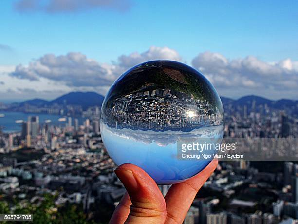 Person Holding Crystal Ball Against Cityscape