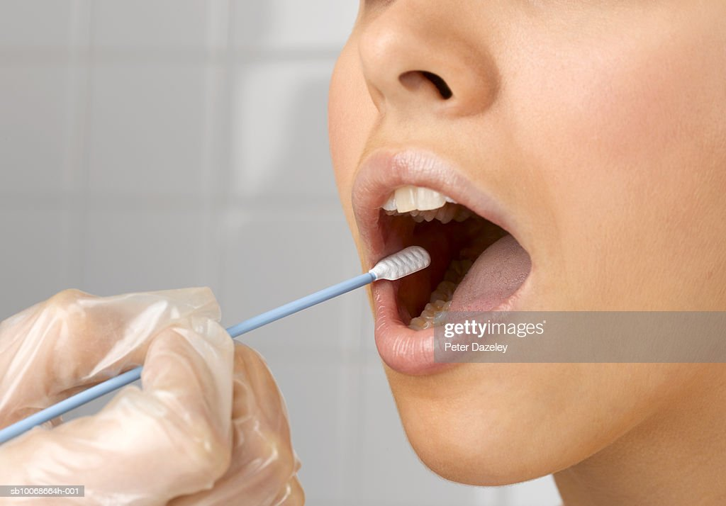 Person holding DNA swab in young woman's mouth, close up of mouth, studio shot : Stock Photo