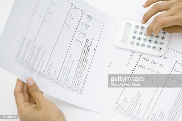 Person holding document, using calculator, cropped view of hands