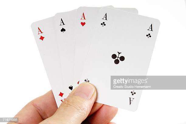 Person holding four aces, close-up