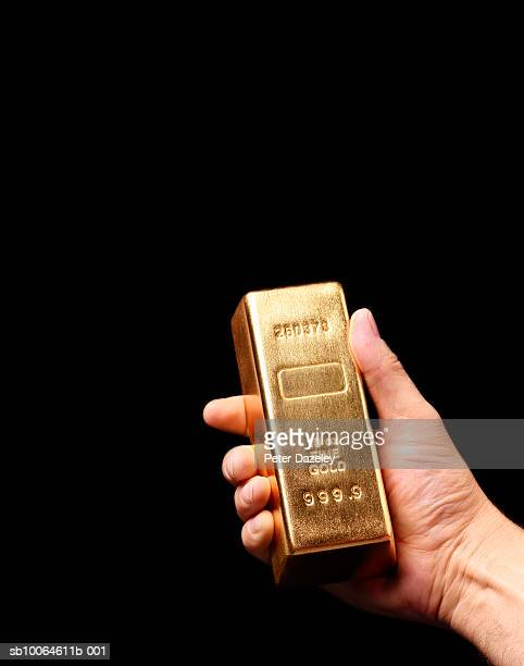 Person holding gold ingot against black background, close-up of hand