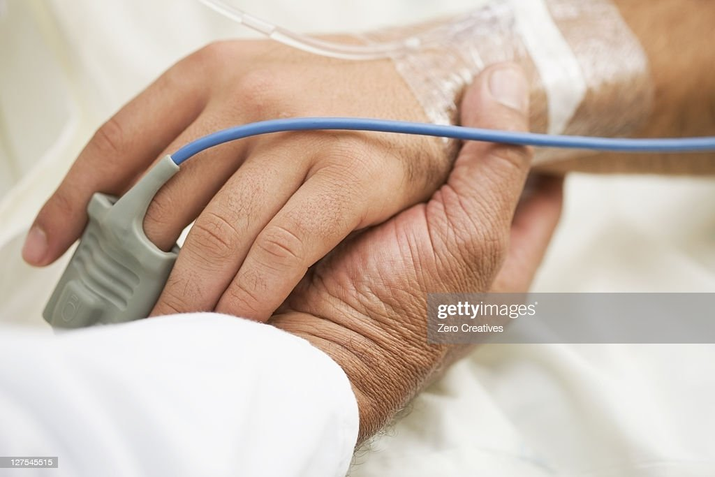 Person holding hospital patients hand : Stock Photo
