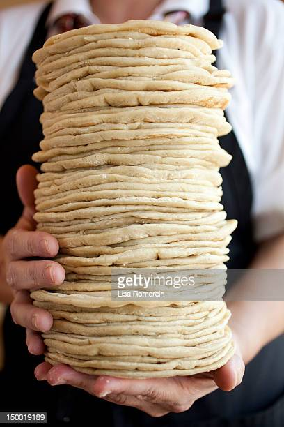 Person holding large stack of hand made tortillas