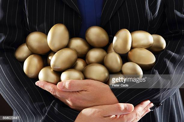 person holding lots of golden eggs in arms.