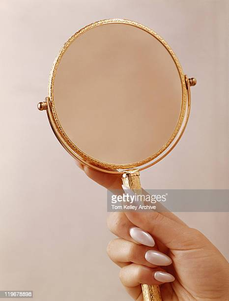 Person holding mirror, close up