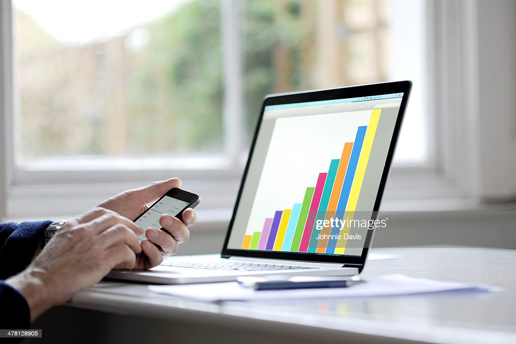person holding mobile phone, laptop with graph