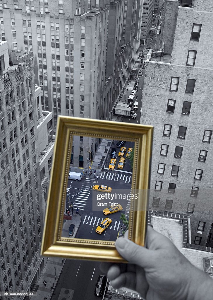 Person holding picture frame framing traffic Manhattan taxis, close-up of hand : Stock Photo