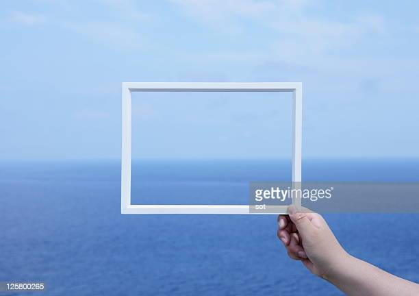 Person holding picture frame in front of ocean