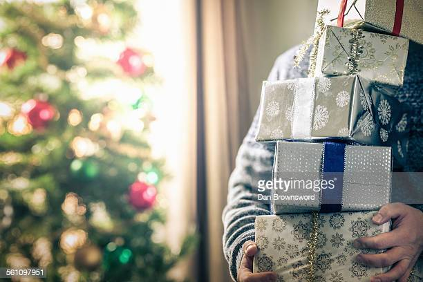 Person holding stack of christmas gifts