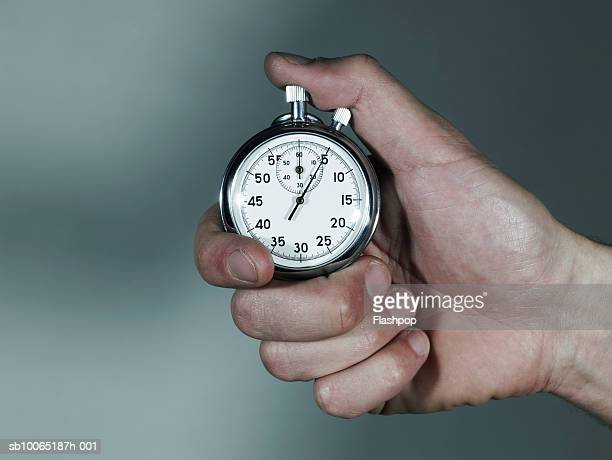 Person holding stopwatch, close-up of hand