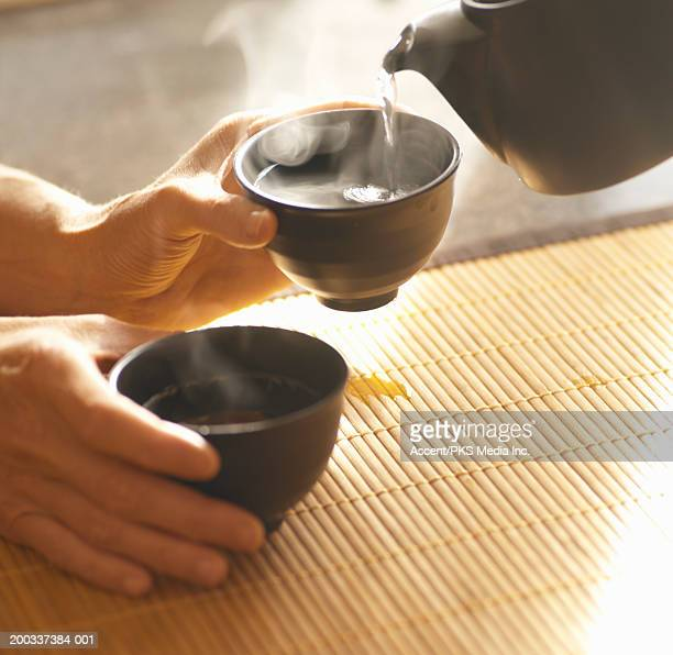 Person holding tea cup while tea is poured, close-up