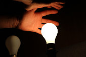 Person holding their hands over a glowing light bulb