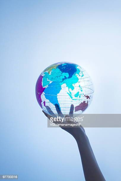 Person holding transparent globe
