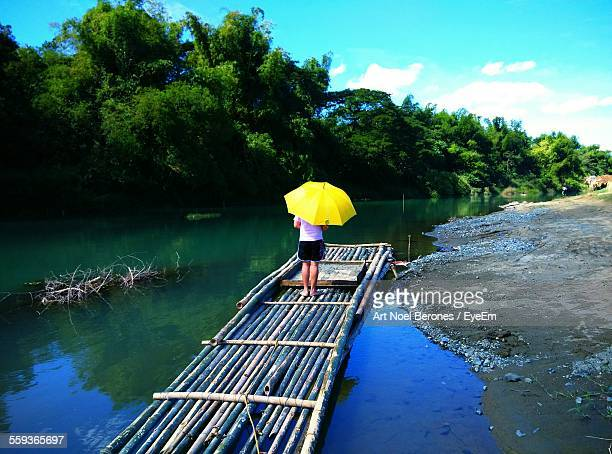Person Holding Umbrella While Standing On Wooden Raft