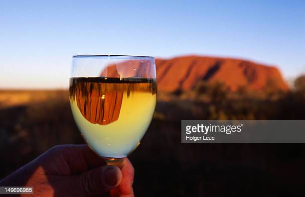 Person holding wine glass in front of Uluru (Ayers Rock).