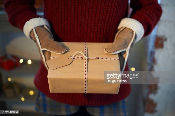 Person holding wrapped Christmas present.