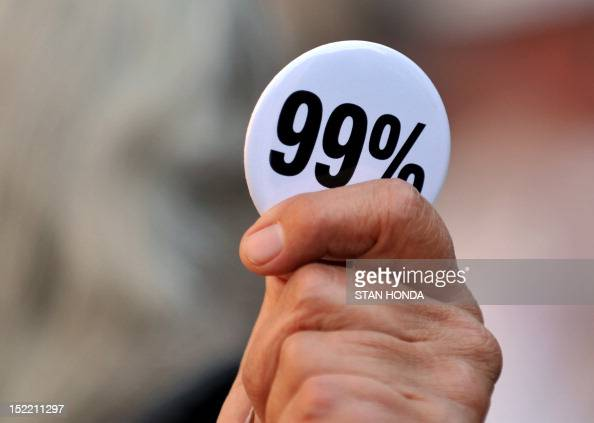 A person holds a 99 Percent button at the Occupy Wall Street protest September 17 2012 on the one year anniversary of the movement in New York AFP...