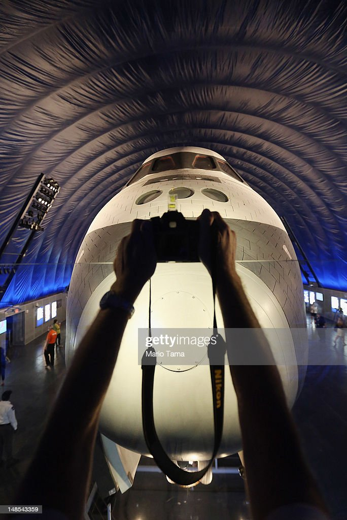 A person holds a camera at the Space Shuttle Enterprise during a press preview of the Intrepid Sea, Air & Space Museum's new Space Shuttle Pavilion on July 18, 2012 in New York City. The Enterprise was NASA's first space shuttle and a prototype which performed tests in 1977 within the Earth's atmosphere. NASA awarded the Enterprise to the museum after the 2011 retirement of the shuttle program. The pavilion will open to the public July 19.