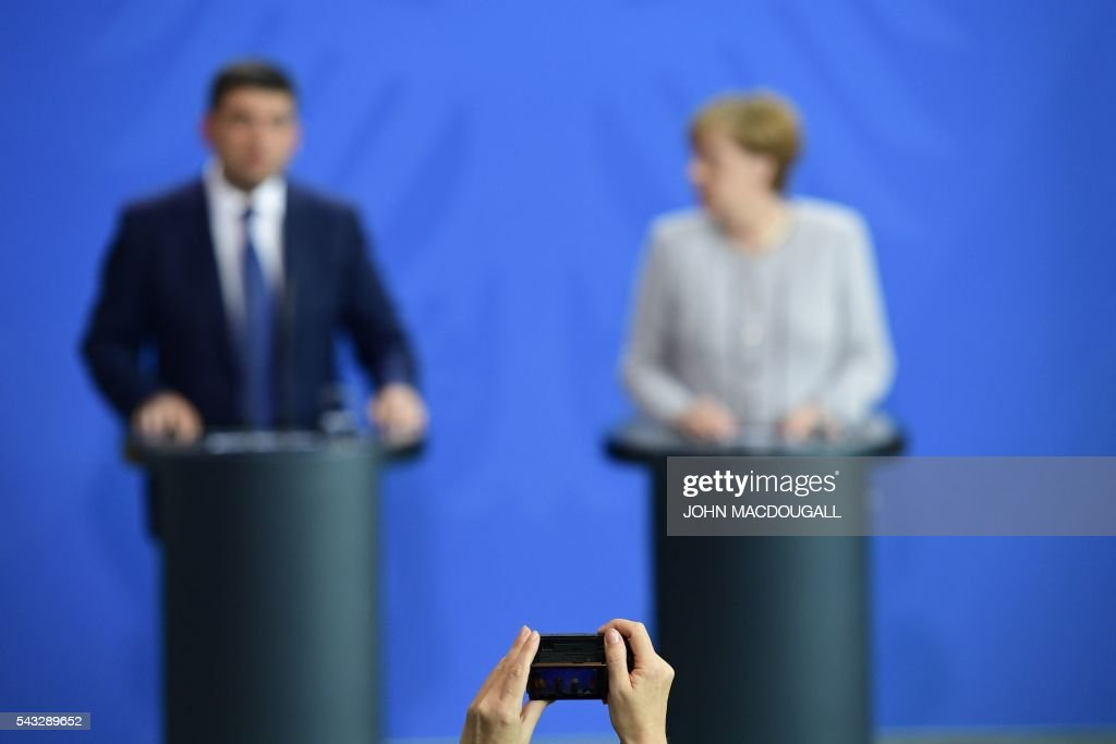 A person holds a camera in front of German chancellor Angela Merkel (R) and Ukraine's Prime Minister Volodymyr Groysman during a joint press conference at the chancellery in Berlin on June 27, 2016. / AFP / John MACDOUGALL