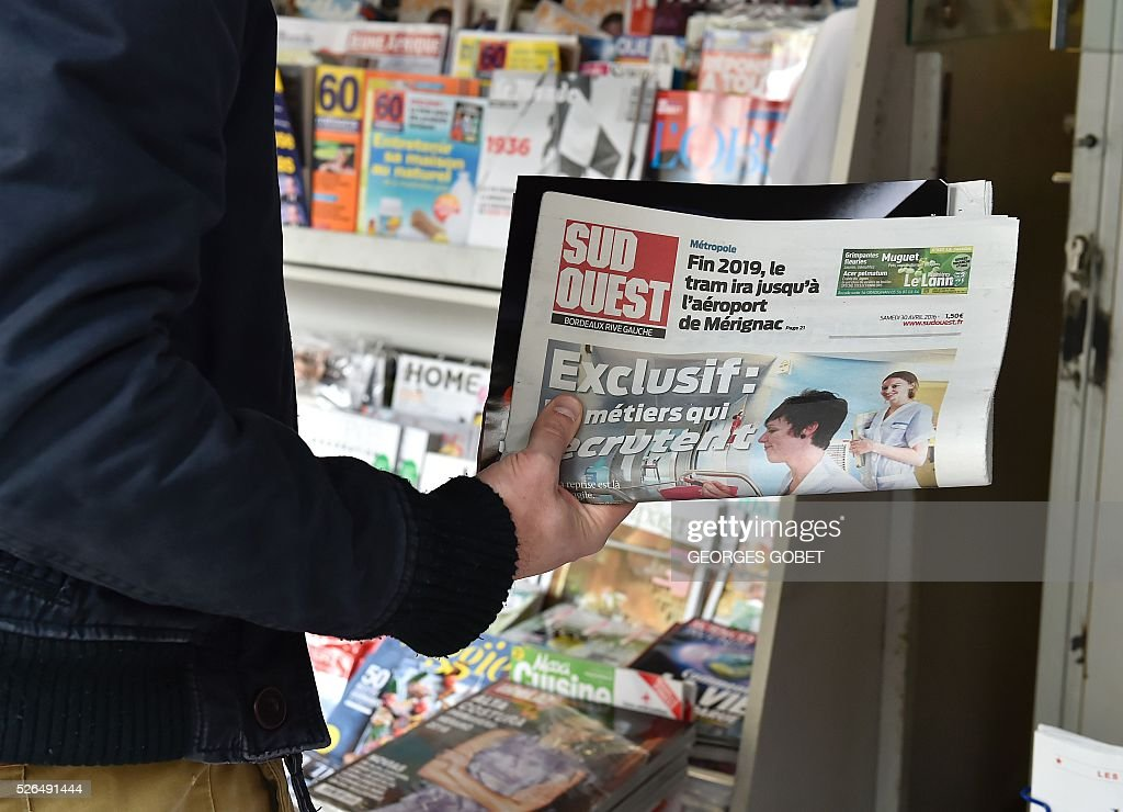A person holds a copy of the French daily newspaper Sud Ouest with its new design in Bordeaux on April 30, 2016. / AFP / GEORGES
