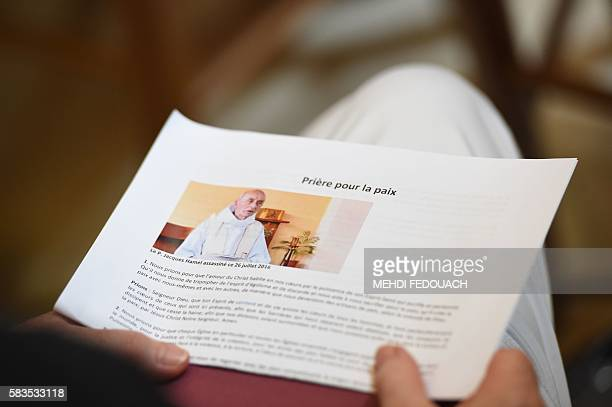 A person holds a document reading 'Prayer for peace' during a mass at the Blessed Sacrament chapel of NotreDame church on July 26 2016 in Bordeaux in...