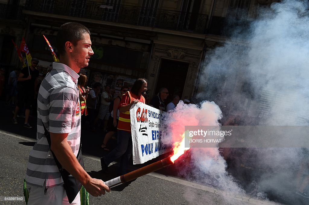 A person holds a flare during a demonstration against the French government's planned labour law reforms, on June 28, 2016 in Marseille, southern France. Unions have called repeated strikes and marches in opposition to the law, which seeks to bring down France's intractable 10-percent unemployment rate by making it easier to hire and fire workers. / AFP / BORIS