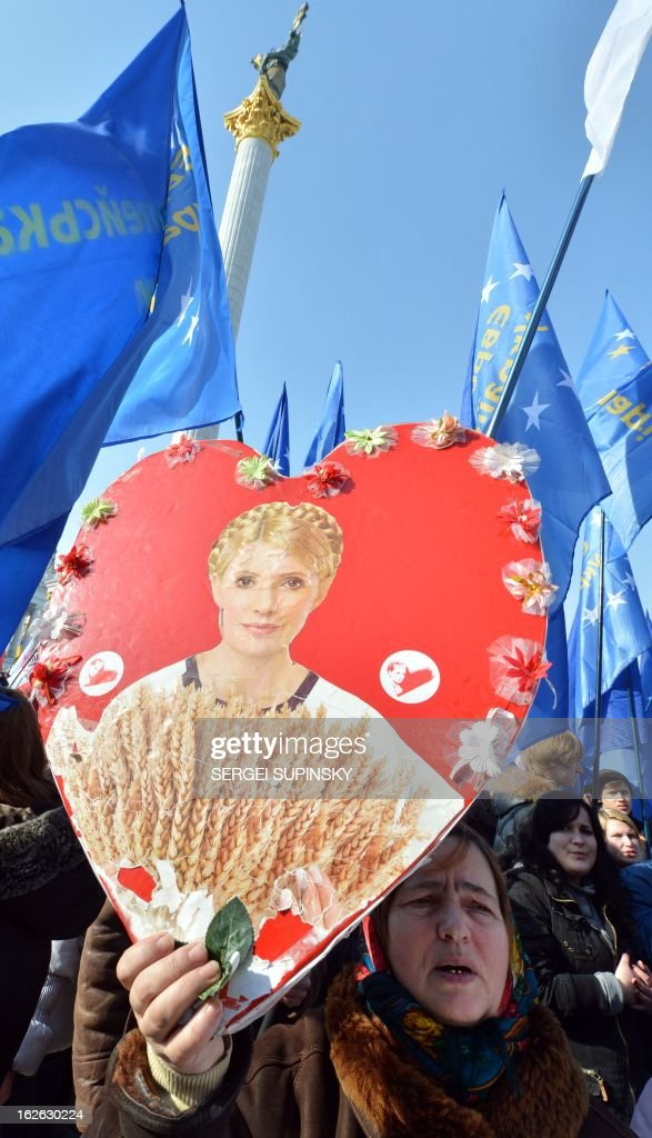 A person (L) holds a heart shaped placard bearing a picture of jailed former Prime minister Yulia Tymoshenko during a rally called by Ukrainian opposition 'against political repression!' on Independence square in Kiev on February 25, 2012, on the day of the start of the 16th Ukraine-European Union summit in Brussels.
