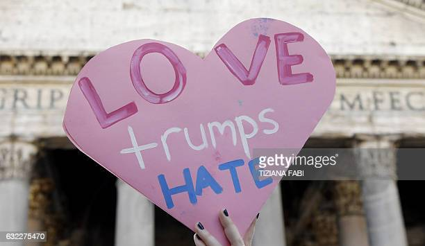 A person holds a heartshaped cardboard during a rally against US newly swornin President Donald Trump in Rome on January 21 a day after Trump's...