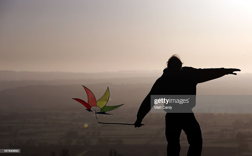 A person holds a holds a windmill as people watch the sun rise as they join in a Beltane dawn celebration service in front of St. Michael's Tower on Glastonbury Tor on May 1, 2013 in Glastonbury, England. Although more synonymous with International Workers' Day, or Labour Day, May Day or Beltane is celebrated by druids and pagans as the beginning of summer and the chance to celebrate the coming of the season of warmth and light. Other traditional English May Day rites and celebrations include Morris dancing and the crowning of a May Queen with celebrations involving a Maypole.