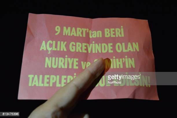 A person holds a leaflet of arrested primary school teacher Semih Ozakca and academic Nuriye Gulmen in Ankara Turkey on July 12 2017 The educators...