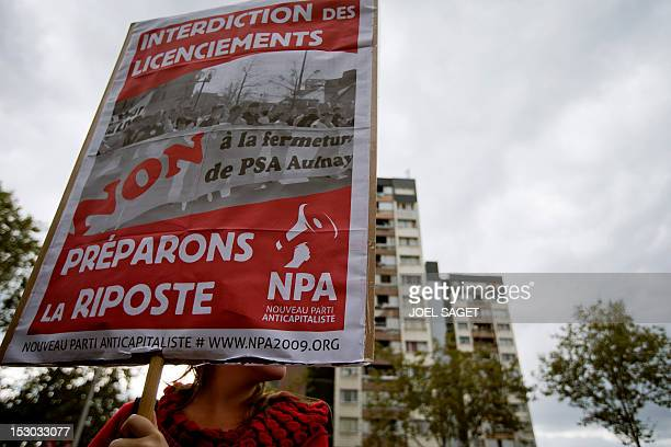A person holds a placard during a demonstration in support to employees of French carmaker PeugeotCitroen and to denounce jobs cut in the...