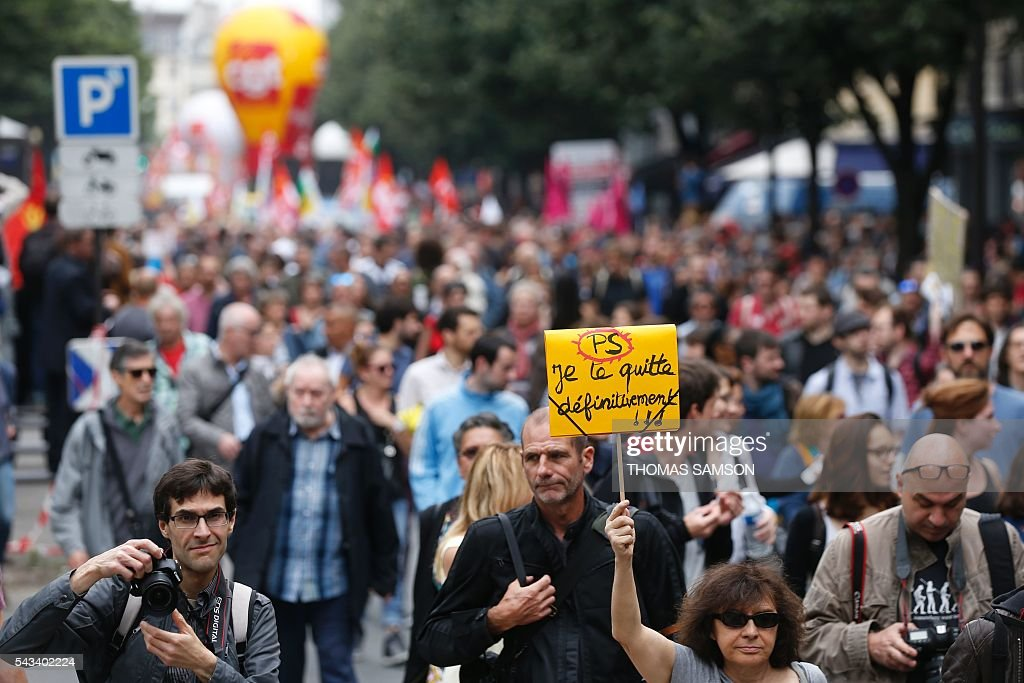 A person holds a placard reading 'Socialist Party (PS) I leave you definitively' take part in a demonstration against the series of controversial labour reforms on June 28, 2016 in Paris. / AFP / Thomas SAMSON