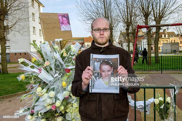 A person holds a portrait of Chloe near a playground on April 16 2015 in Calais northern France in homage to a nineyearold girl who was killed a day...