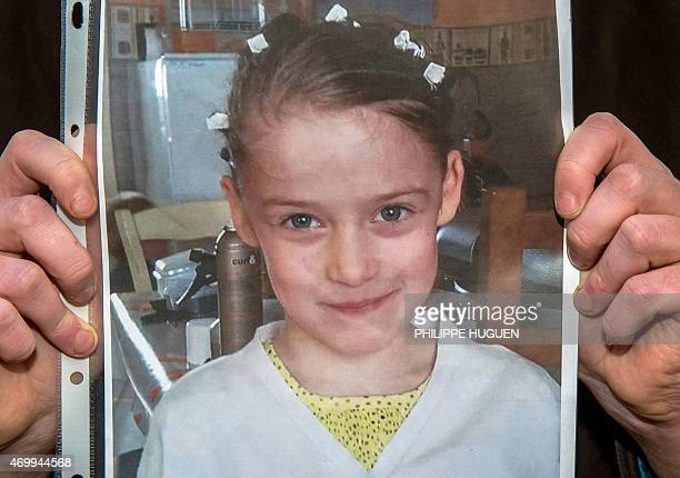 A person holds a portrait on April 16 2015 in Calais northern France in homage to a nineyearold girl who was killed a day before A Polish man has...