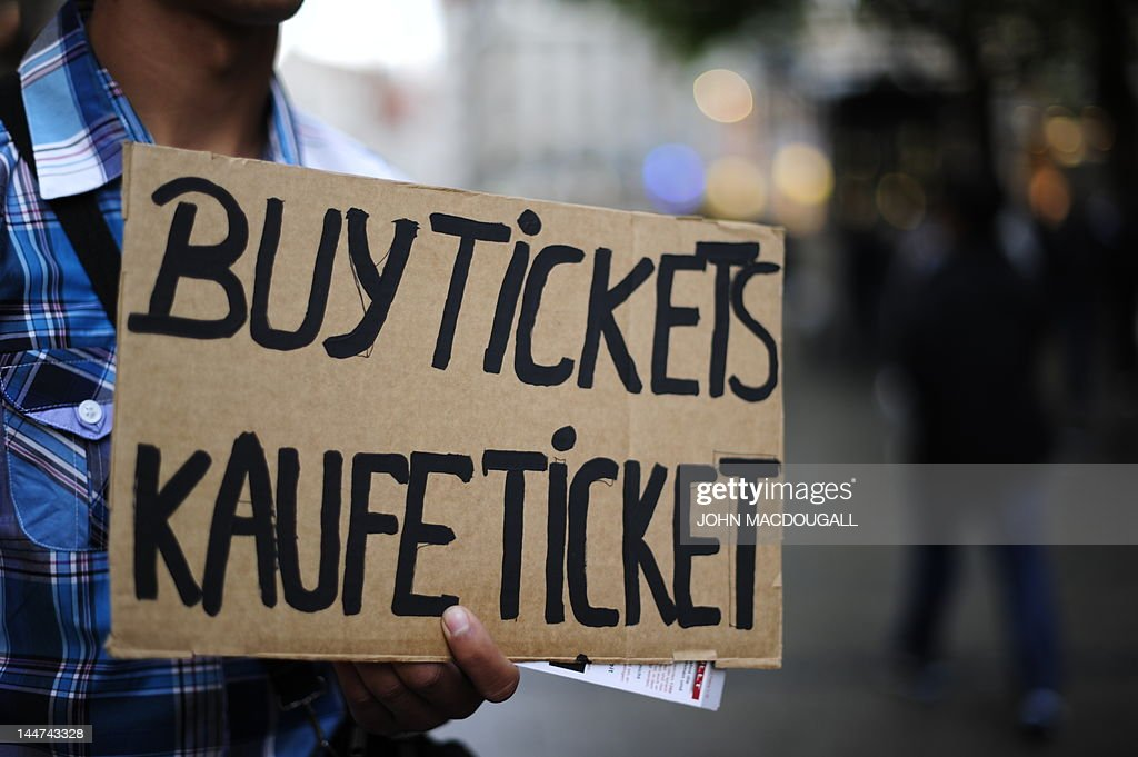 A person holds a poster asking for buying ticket screening for the UEFA Champions League final football match FC Bayern Muenchen vs Chelsea FC in...