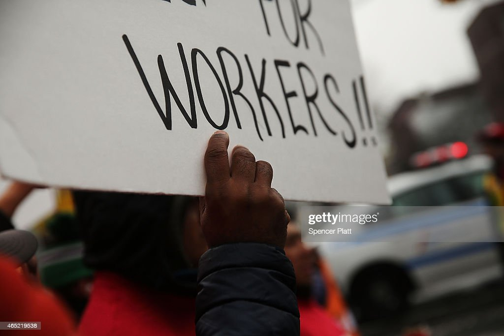 A person holds a sign during a march to the Vegas Auto Spa a car wash that has become a focal point for labor and union rights during a rally on...