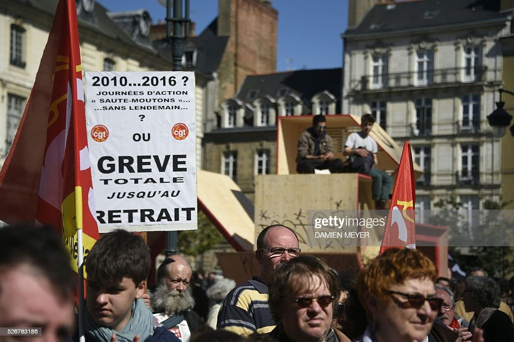A person holds a sign during a May Day rally in Rennes, western France, on May 1, 2016. / AFP / DAMIEN