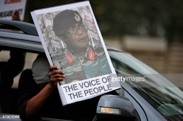 A person holds a sign featuring Commander of the Zimbabwe Defence Forces Constantino Chiwenga as people take part in a demonstration demanding the...