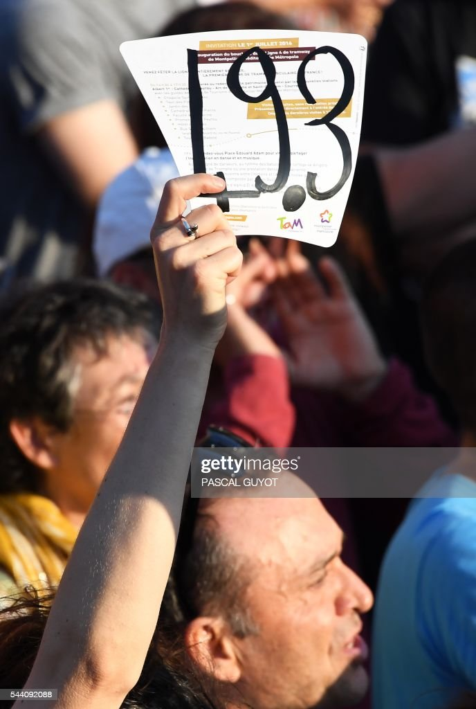 A person holds a sign reading '49.3' during the speech of the French Prime Minister for the inauguration of the tram line 4 on July 1, 2016, in Montpellier, southern France. / AFP / PASCAL