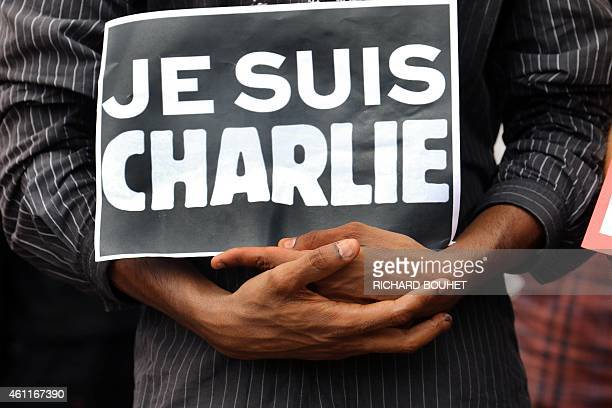 A person holds a sign reading in French 'I am Charlie' during a gathering of hundreds people at the Human Rights square in SaintDenis de la Reunion...