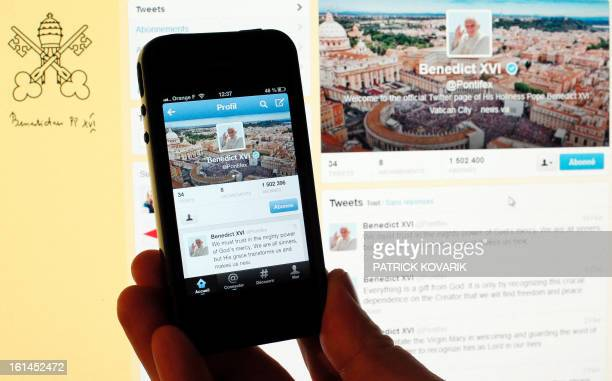 A person holds a smartphone displaying the twitter account of pope Benedict XVI on February 11 2013 in Paris Pope Benedict XVI announced on February...