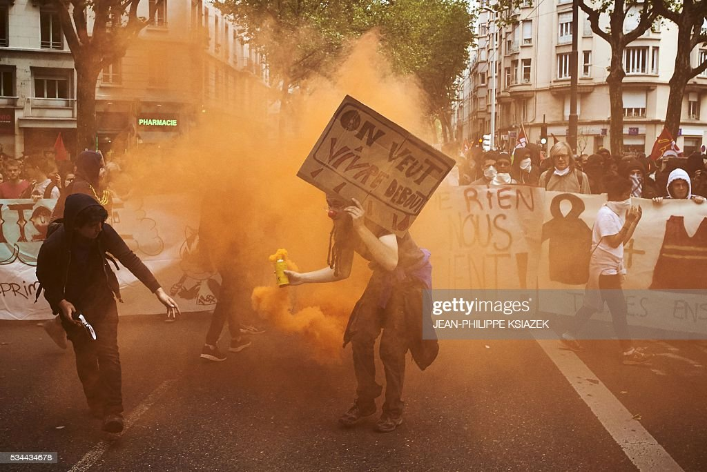 A person holds a smoke and a placard which translates as 'We want to live up' during a demonstration against the government's planned labour reform, on May 26, 2016 in Lyon, central eastern France. The French government's labour market proposals, which are designed to make it easier for companies to hire and fire, have sparked a series of nationwide protests and strikes over the past three months. Masked youths clashed with police in Paris and striking workers blockaded refineries and nuclear power stations on May 26, 2016 as an escalating wave of industrial action against labour reforms rocked France. KSIAZEK