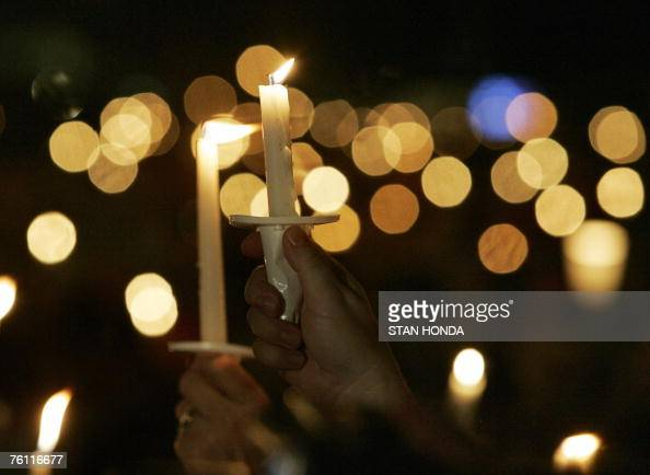 A person holds aloft a candle during a candlelight vigil at Graceland the home of Presley 15 August 2007 in Memphis Tennessee on the eve of the 30th...