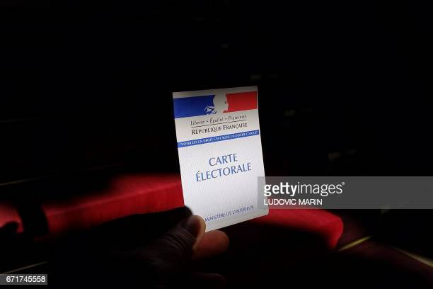 A person holds an electoral card in Paris on April 23 on the first round of the Presidential elections / AFP PHOTO / Ludovic MARIN